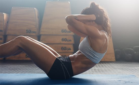 hard ab workout woman balancing on sacrum demonstrating crunch