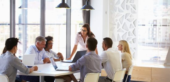 leadership skills woman standing at head of conference table speaking