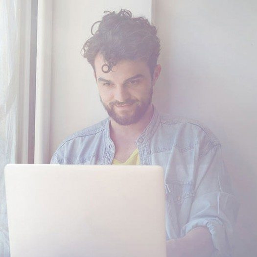 get more done man sitting by window working on laptop