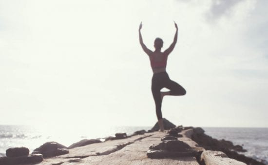 peak state woman in tree pose near ocean