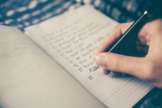get motivated person writing a checklist in notebook