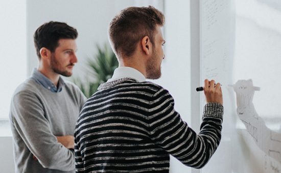 business results man drawing on whiteboard next to other man