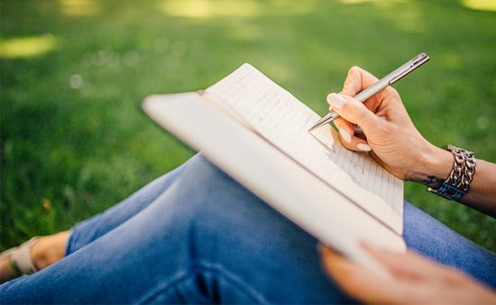 personal growth woman writing in journal on grass