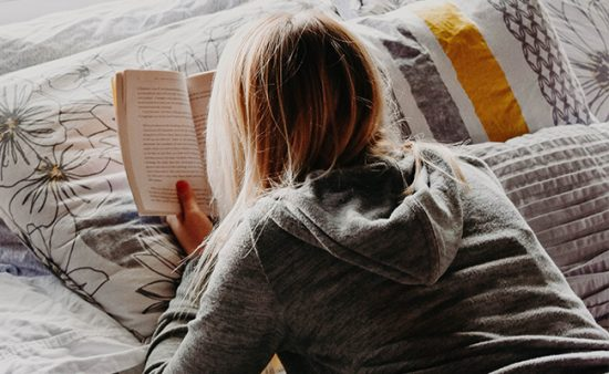 good habits girl laying on bed reading book