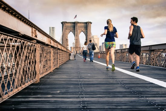 two people running on a bridge