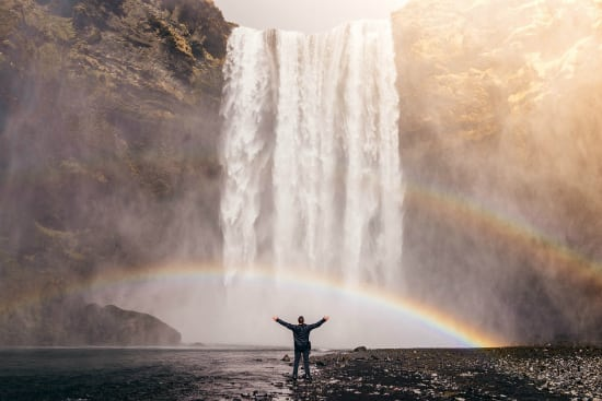 man thinking positive in front of a waterfall and rainbow