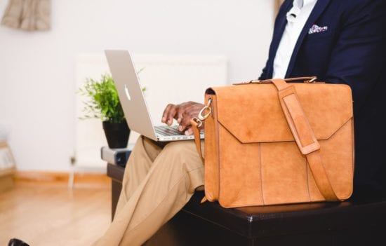 a man with a red bag is working on his macbook